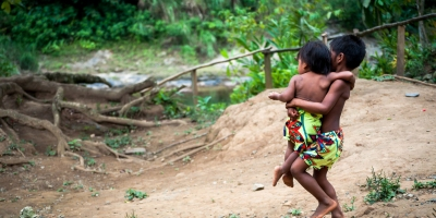 Young indigenous boy carries his litter sister down to the water.